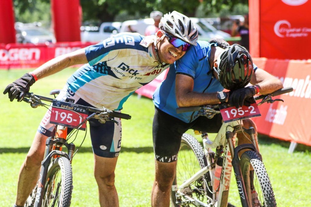 Gareth O'Connell congratulates his exhausted teammate Andrew Soutar upon crossing the finish line of the Momentum Health Tankwa Trek, presented by Biogen, on Sunday the 12th of February 2017.