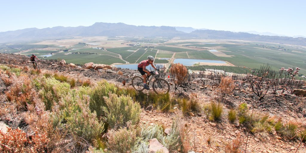 Matt Osborne and Nico Van Zyl crest the climb to the highest point on the Stage 1 route, with the orchards of the Witzenberg Valley floor far below them in the background, of the Momentum Health Tankwa Trek, presented by Biogen, on 10 February 2017.